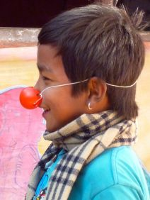 Young man sings with red nose.