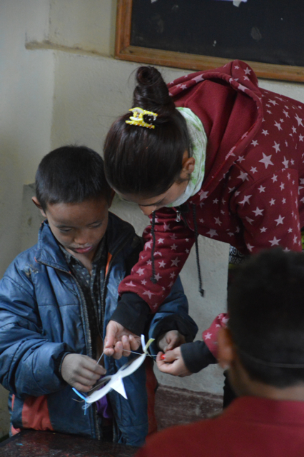 UEMS worker Seetha helping a child put elastic on his mask.